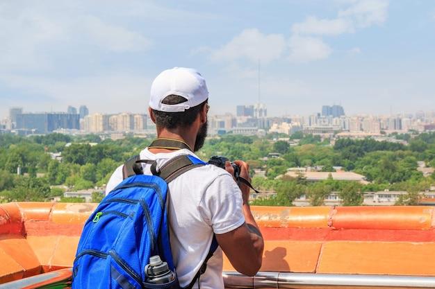 白いtシャツと帽子をかぶった男性旅行者が、中国の首都、北京の景山公園の望楼から街の風景の写真を撮ります