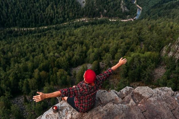 男性の旅行者が森の鳥瞰図で岩の上に座っています。旅行、冒険のライフスタイル、休暇。崖の端に座っている男の旅行者。男は美しい景色を楽しむ