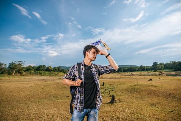 地図を運んで草原に立っているバックパックを持つ男性旅行者。