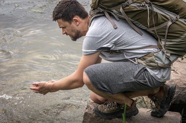 Путешественник с большим походным рюкзаком пьет воду из горной реки.