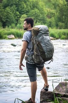 У реки стоит мужчина-путешественник с большим походным рюкзаком.