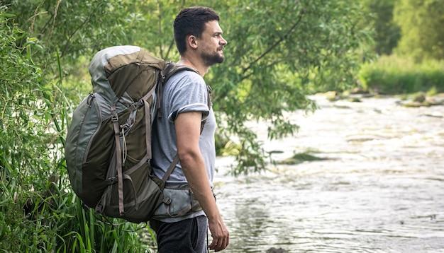 큰 하이킹 배낭을 메고 있는 남성 여행자가 강 근처에 서 있습니다.