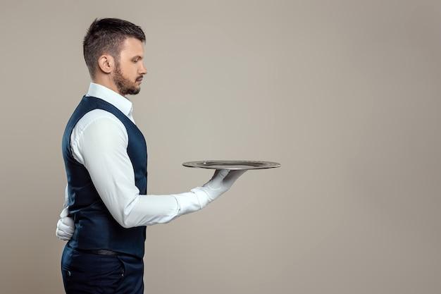 Официант в белой рубашке стоит боком с серебряным подносом. концепция обслуживающего персонала, обслуживающего клиентов в ресторане.