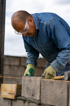 そよ風のブロックで壁を構築する男性労働者