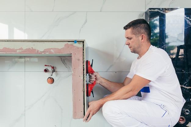 Рабочий монтирует большую керамическую плитку в ванной