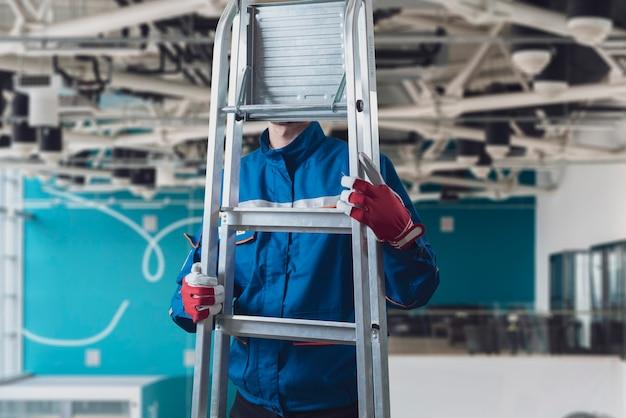 はしごを持って運ぶ建設現場の男性労働者