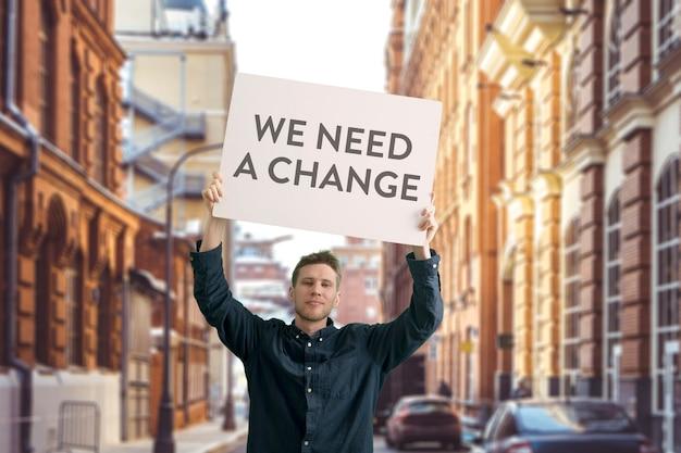段ボール、単独抗議、政治的ジェスチャー、ポスターを示す男性の若い活動家