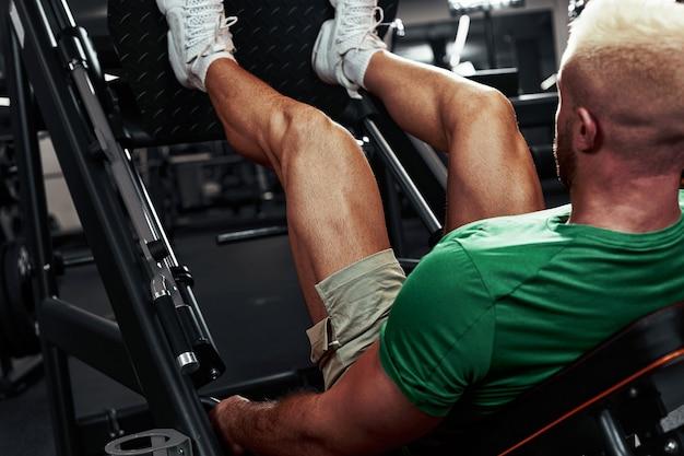 男、ボディービルダーは彼の足で運動をします。アスリートはシミュレーターのジムで足を鍛えます。