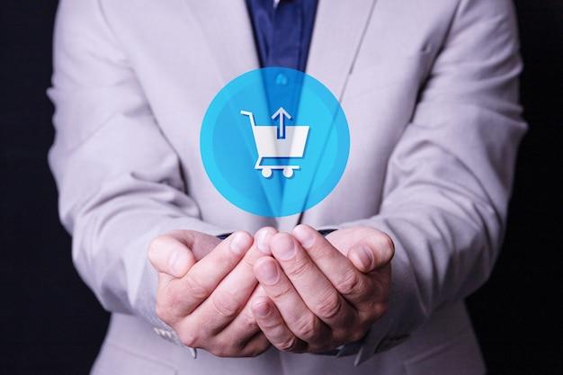 男性、ビジネスマンは彼の手のひらに買い物かごのロゴを持っています。