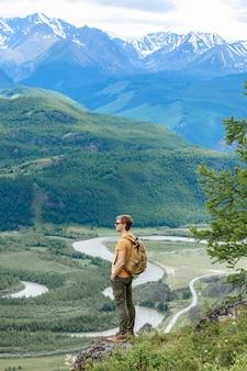 배낭을 메고 산 정상에 오른 남자 관광객은 계곡의 경치를 즐길 것입니다.