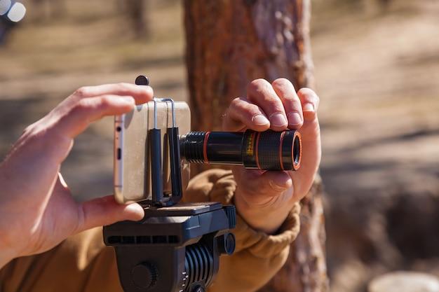 Мужчина настраивает смартфон на штативе с объективами фотограф путешествует, делая снимки