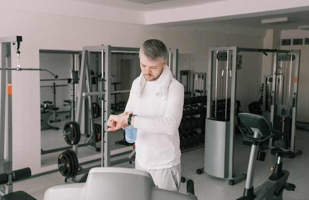 激しいトレーニングの後の男は、スマートウォッチを見ます。カーディオロード