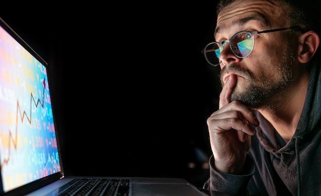 株式市場を分析している男性が電子ボード上の財務データをグラフ化する