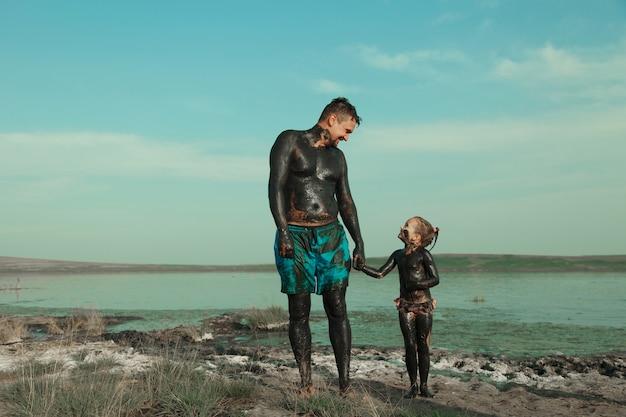 男と子が粘土にまみれている