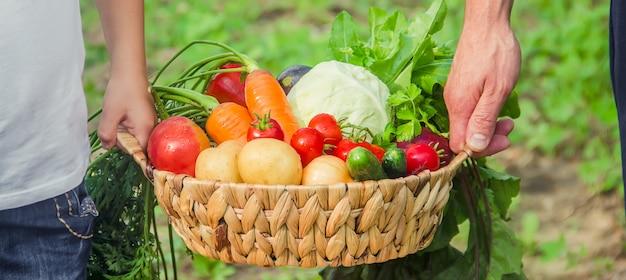 手に野菜を持って庭にいる男と子供。