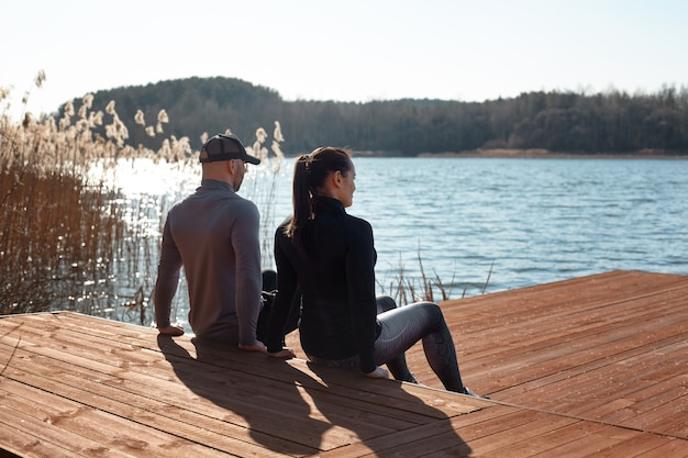 Мужчина и девушка делают обратный отжимание. пара занимается спортом на озере. фитнес, спорт, стиль жизни