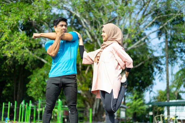 Мужчина и девушка в платке в спортивной одежде вместе растягивают ноги и руки в парке.