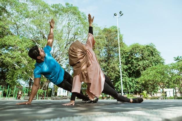 공원에서 지구력 훈련을 위해 함께 손 운동을하는 체육관 옷을 입은 베일에있는 남자와 여자