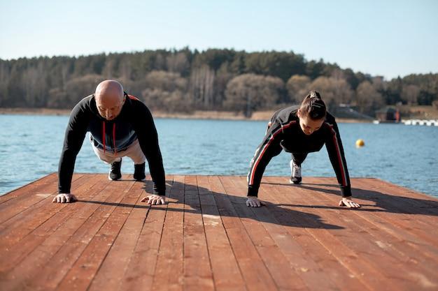 Мужчина и девушка в спортивной одежде выполняют упражнения на доске на пристани у озера. спорт, здоровье, активные хобби