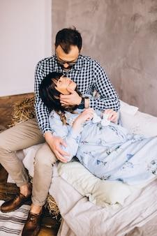 집에서 소파에 앉아있는 남자와 임신 한 여자