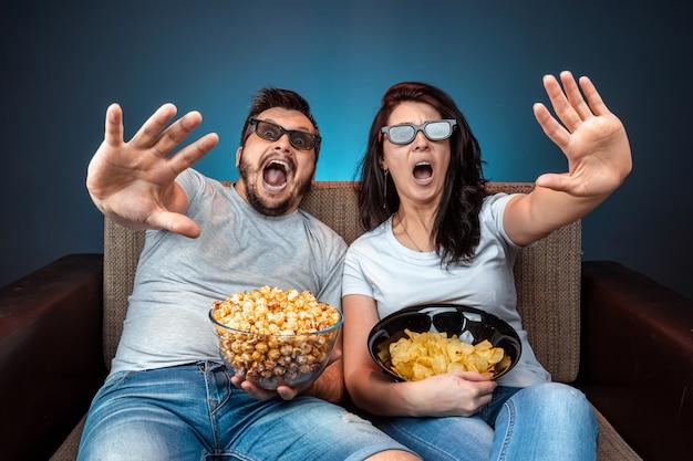 男と女、映画を見ている家族、3dメガネのシリーズ、青い壁。映画、映画、感情、驚き、レジャー、ストリーミングプラットフォームの概念。
