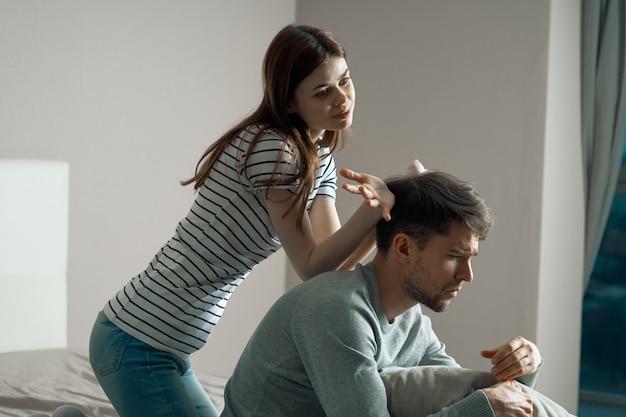 Мужчина и женщина сидят на кровати и говорят об отношениях, настоящей ссоре
