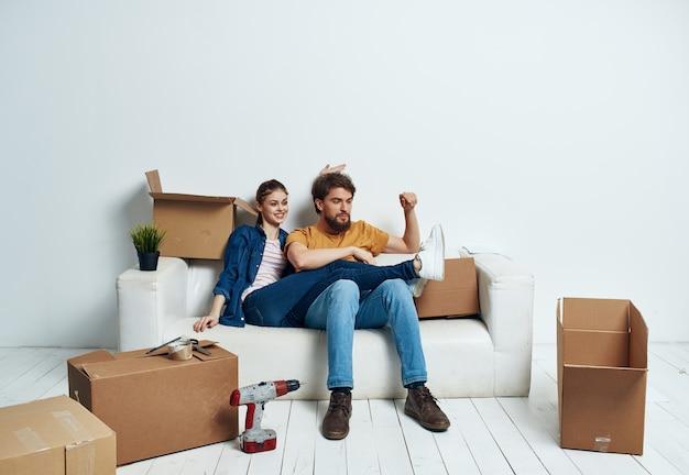 남자와 여자가 상자 근처의 소파에 앉아 물건이 움직이고 있습니다.