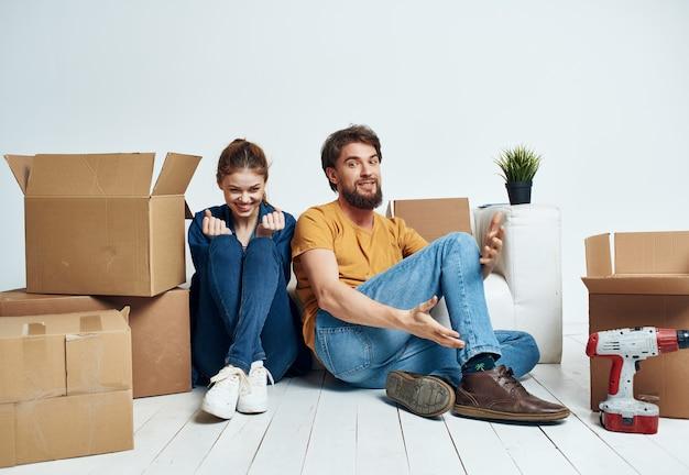 남자와 여자는 새 아파트에서 리노베이션을 움직이는 물건으로 바닥 상자에 앉아 있습니다.