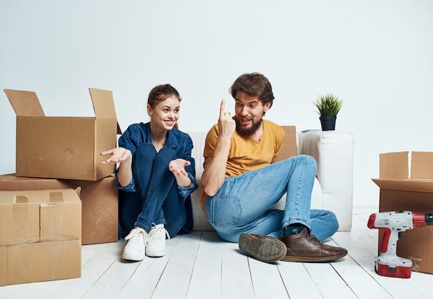 Мужчина и женщина сидят на полу в помещении возле дивана и перемещают коробки.