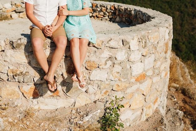 Мужчина и женщина сидят бок о бок на краю каменной платформы. фото высокого качества