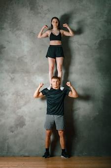 한 남자와 한 여자 선수가 회색 배경에 서로의 위에 서 있습니다.
