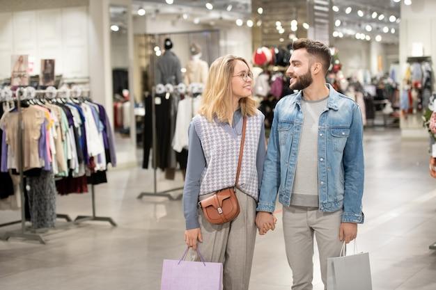 衣料品店を歩きながらおしゃべりする男女