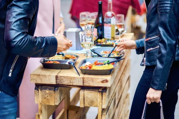 男性と女性が屋台の食べ物を食べます。焼きポレンタとワイン