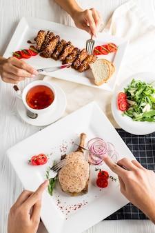 男と女がレストランで昼食をとる。サーブされたテーブル。