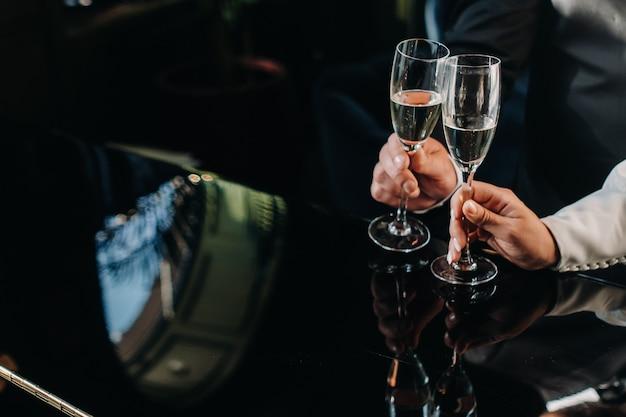한 남자와 한 여자가 그들의 손 클로즈업에 샴페인 잔을 들고 있습니다.