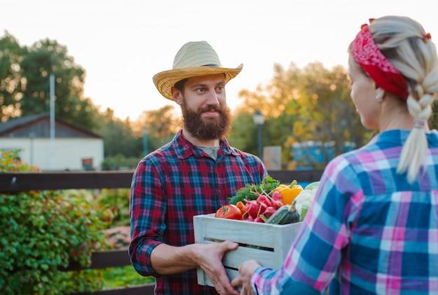 農場野菜の収穫の入った箱を持った男女