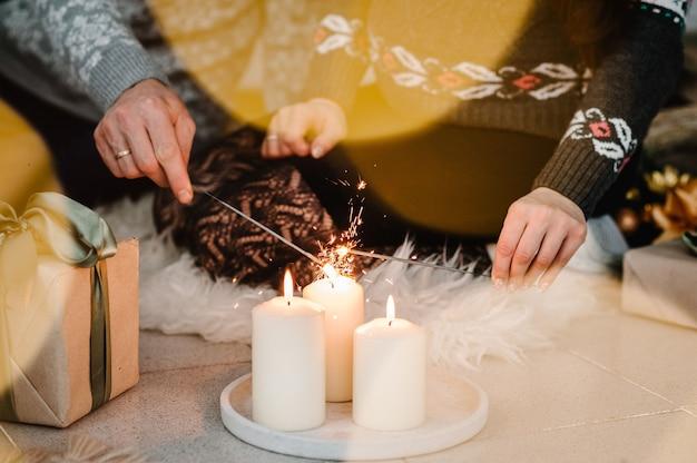 男性と女性がクリスマスツリーの近くで線香花火に火をつけます。家の装飾。メリークリスマスとハッピーホリデー!クリスマス。