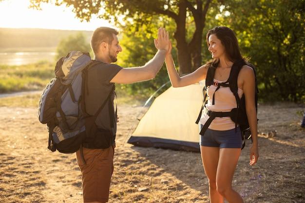 日没のテントの近くにバックパックを備えたハイキング旅行の男女5人。自然の中の新婚旅行