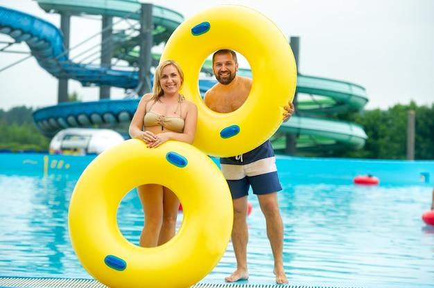 고무 풍선 원 안에있는 남자와 여자는 여름 워터 파크 수영장의 배경에 서 있습니다.