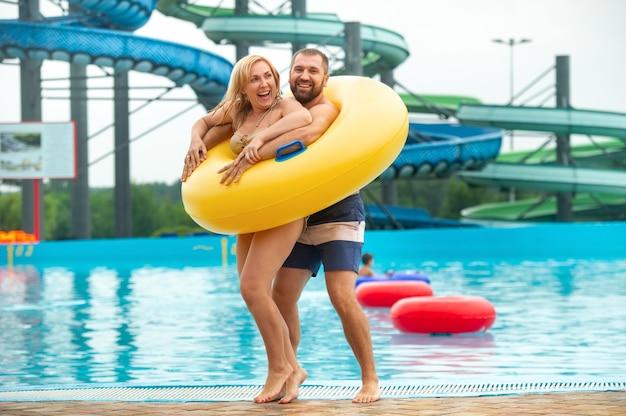 Мужчина и женщина в резиновом надувном круге стоят на фоне бассейна летнего аквапарка