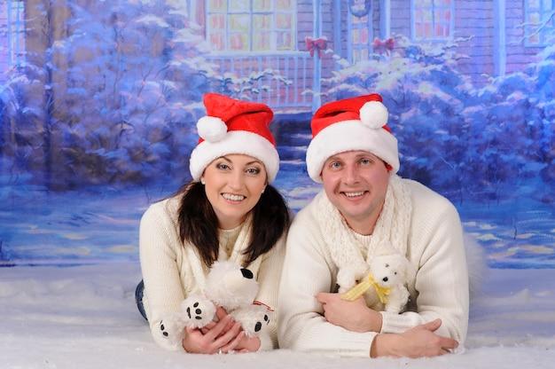 クリスマスの帽子をかぶった男と女が雪の中に横たわっています。