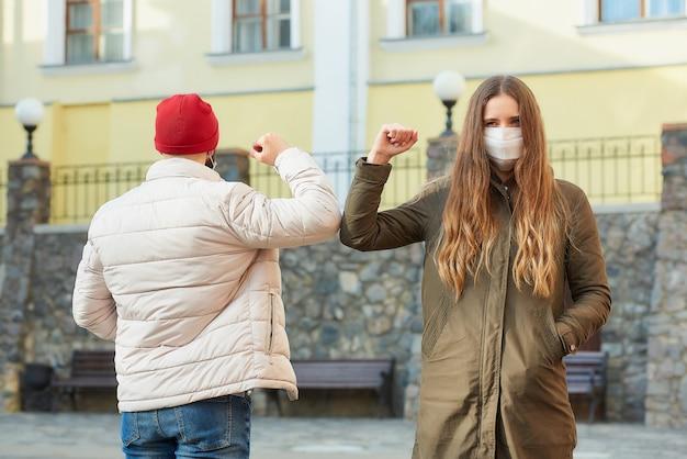 ハグで挨拶する代わりに顔のマスクをした男性と女性がバンプエルボー