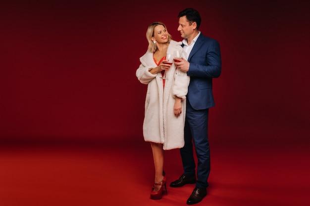 Мужчина и женщина, влюбленные с бокалом шампанского на красном фоне обнимаются.
