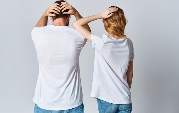 같은 티셔츠와 청바지를 입은 남녀가 손으로 몸짓을하고 있습니다.