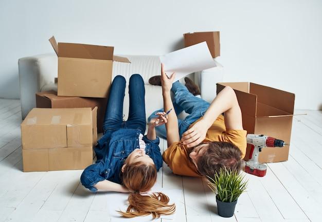 남자와 여자는 이동하는 방을 수리하는 상자 옆 바닥에 누워 있습니다. 고품질 사진