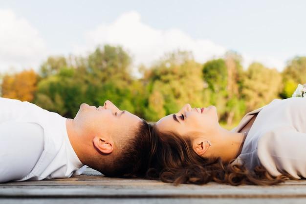 Мужчина и женщина лежат на деревянной поверхности лицом к лицу и улыбаются на фоне природы