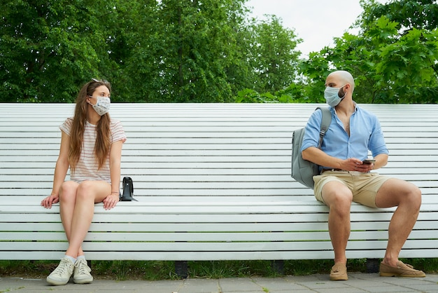 Мужчина и женщина смотрят друг на друга, сидя на противоположных концах скамьи, держась на расстоянии друг от друга, чтобы избежать распространения коронавируса.