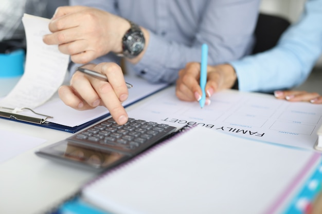Мужчина и женщина составляют семейный бюджет на основе счетов. крупный план, мужские руки нажимают на калькулятор, женские руки делают записи.