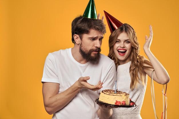 축제 모자에 컵 케이크와 촛불 생일에 남자와 여자는 재미와 함께 휴가를 축하, 행복한 커플