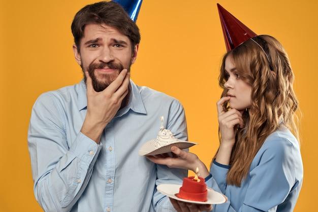 カップケーキとお祝い帽子のキャンドルで誕生日に男女が楽しんで、休日を一緒に祝う